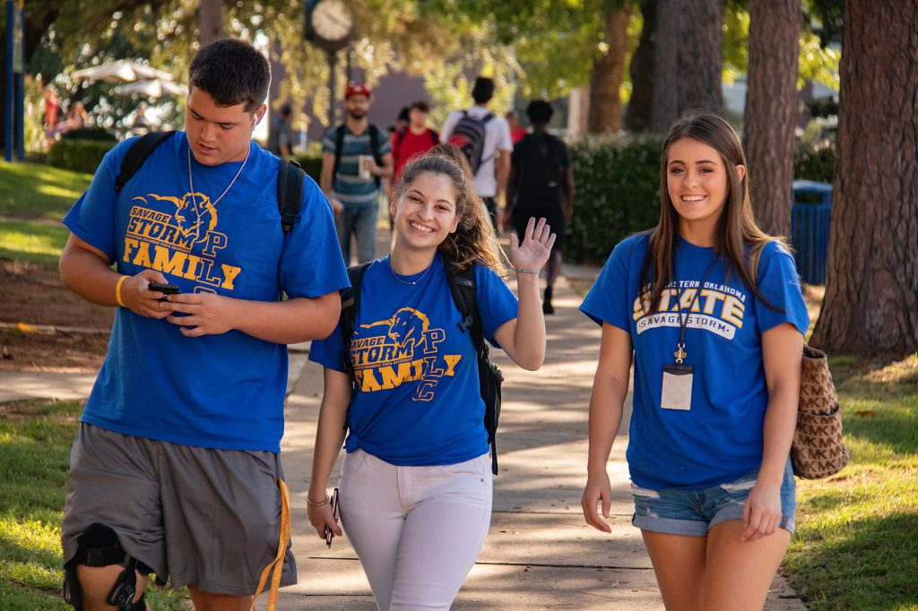 Three students waving on camps